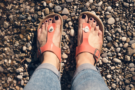 Womans feet in orange sandals and jeans standing on the pebble beach