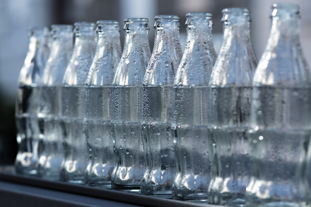Raw of white, empty glass bottles, wet and washed Stock Photo