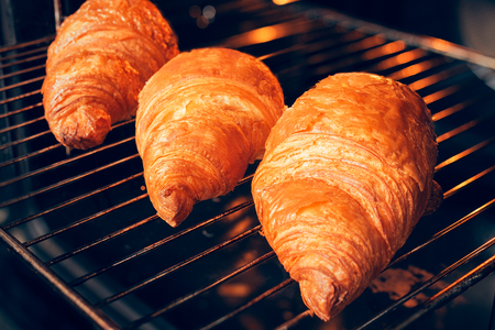 Freshly baked croissants on the oven rack in the oven