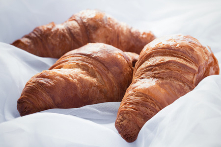 Three homemade croissants laying on white sheets