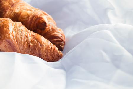 Homemade croissants laying on white sheets