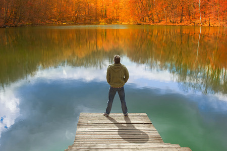 Lonely man standing on the edge of the small wooden pier looking at the lake and colorful forest on the other side Stock Photo - 100806806