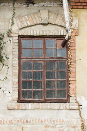 Old window on old building facade, with decorative brick frame and arch and chimney coming out from window frame