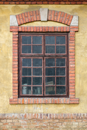 Old window on yellow building facade, with decorative brick frame and arch