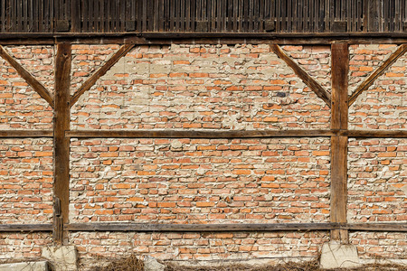 Old red brick wall with support wooden beams