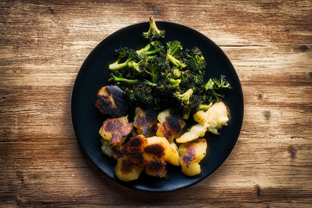 Black plate filled with roasted broccoli and potatoes on rustic wooden table