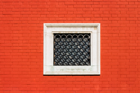 Red brick wall with small white window with decorative iron gratings Stock Photo - 101028420