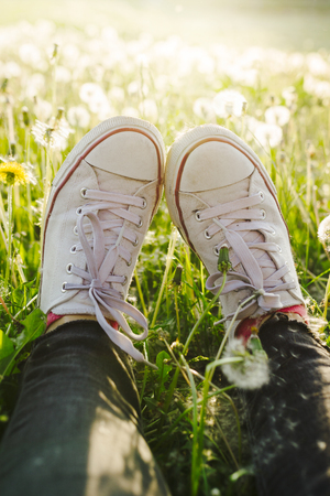 Female legs in white canvas sneakers and black jeans laying in the meadow full of white dandelions Stock Photo