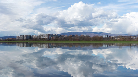 Zagreb city skyline across river Sava and with mountain Medvednica in background, clouds reflecting in water