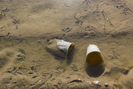Plastic cups dumped in shallow waters on a sandy beach Stock Photo - 101410710
