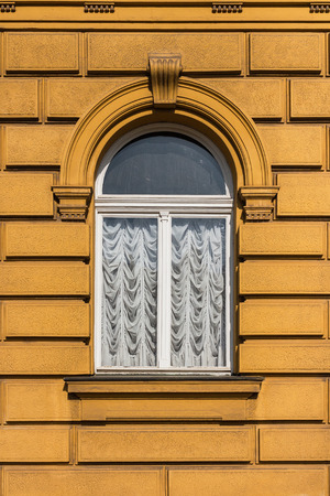 Retro looking old, yellow facade building  with arched window with white curtains Stock Photo - 101410711