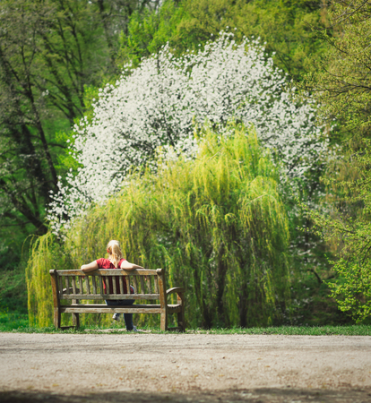 Blonde woman in red shirt sitting on wooden bench in park, looking at lush trees, one with white blossoms Stock Photo - 102254355