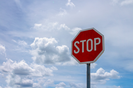 Red stop sign and blue sky with white clouds in background Stock Photo - 102205720