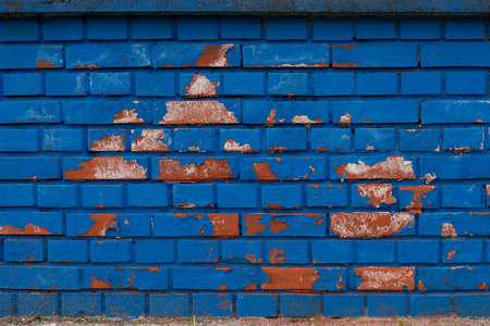 Blue brick wall, weathered and rough with patches of orange bricks coming through Stock Photo