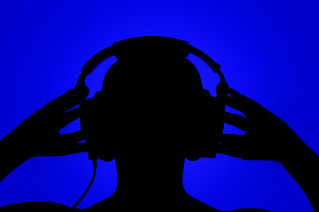 Silhouette of man with headphones on blue background, listening to music Stock Photo