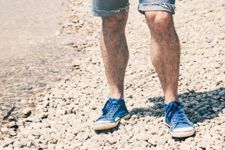 Male legs in blue canvas sneakers and blue cut off jeans shorts standing on the pebble beach near the water Stock Photo - 102948258