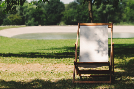 Deck chair under the tree, on grass lawn near the lake, vacation spot Stock Photo - 103008032