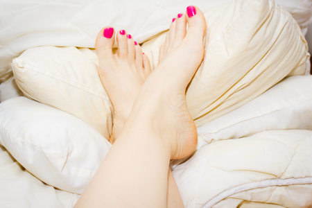 Womans feet, up on the pile of soft pillows, bare with pink nail polish on toe nails