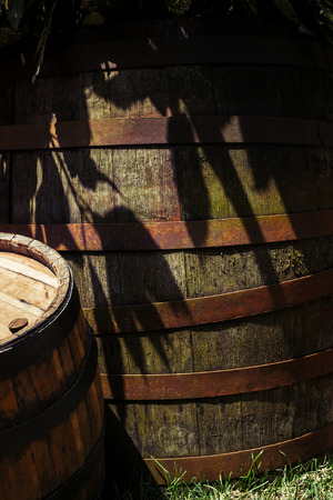 Old wooden barrel in the tree shade in the garden with smaller barrel on the side Stock Photo - 102958070