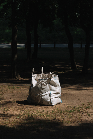 White garbage bag left in the park Stock Photo - 103686936