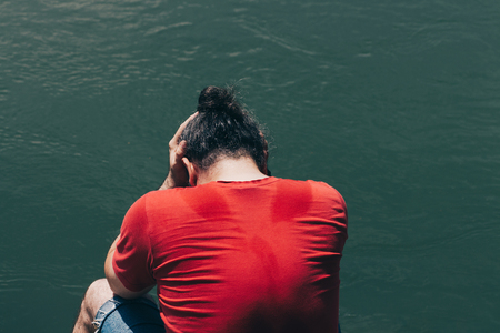 Sad, depressed man in red shirt sitting bay the murky green water, holding his hands on his had Stock Photo - 103686937