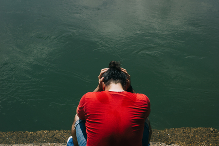 Sad, depressed man in red shirt sitting bay the murky green water, holding his hands on his had Stock Photo - 103686939