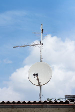White satellite dish on an old roof top Stock Photo