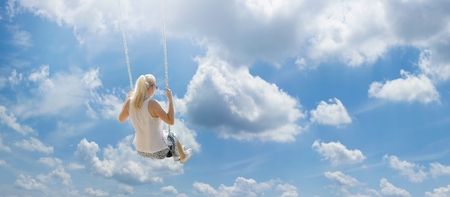 Blonde girl with ponytail flying high among the white clouds on a swing