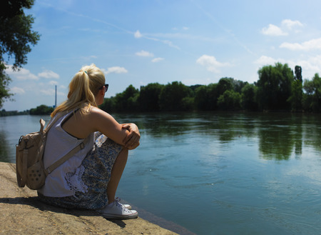 Blonde woman with pony tail, sitting by the river in white shirt and blue skirt, with small backpack on her back Stock Photo - 103907493