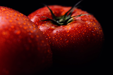 Two red, ripe tomatoes, washed, still with water droplets on them, on black background Stock Photo