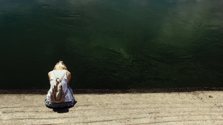 Blonde hair woman sitting by the dark river water, sad, depressed and lonely, crying