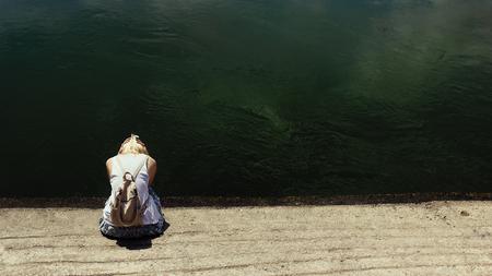 Mujer de cabello rubio sentada junto al agua del río oscuro, triste, deprimida y sola, llorando