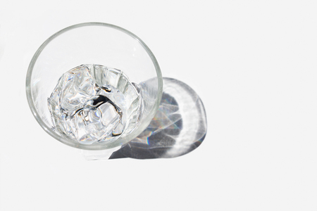 Cold glass of water with ice cubes in it on with shadow, on white background