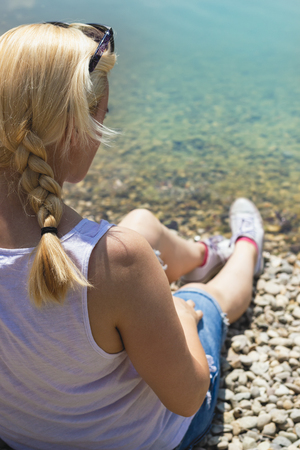 Woman with blonde braided hair in white shirt and cut off jeans, sitting on a beach near turquoise water Stock Photo