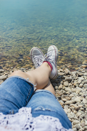Female legs in jean shorts and white canvas sneakers laying on the beach near the turquoise water Stock Photo - 105804987