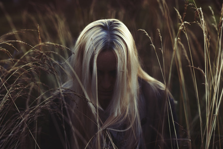 Woman with long blonde hair bowing her head in tall grass field in the dark, face hidden in the shadow Stock Photo