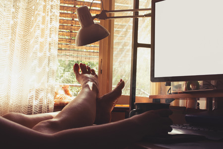 Woman sitting with  bare legs on a table, drinking coffee in front of PC monitor, enjoying sunshine thru open window Stock Photo - 105940082