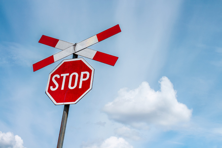 Red stop sign with railway cross sign and blue sky with white clouds in background Stock Photo
