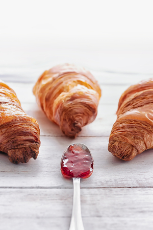 Three croissants on a white wooden table with spoon filled with jam in the middle Stock Photo - 105940107
