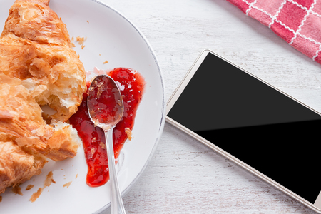 Croissant with jam on white plate and white kitchen table, with red napkin and cell phone beside it Stock Photo - 105940108