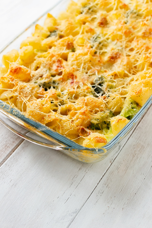 Pasta and broccoli casserole in glass oven dish on white kitchen table Stock Photo - 105940117