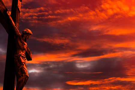 Jesus on a cross against burning red sunset sky with clouds and little patches of light coming through Stock Photo