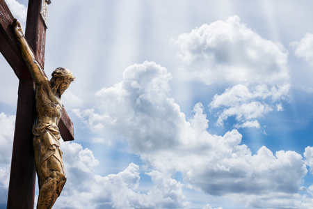 Jesus on a cross against blue sky with white clouds and rays of light coming thru Banque d'images