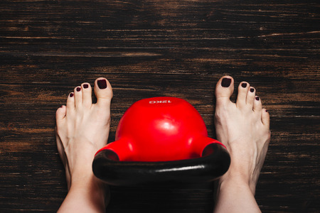 Woman standing bare foot with red kettlebell between her legs on dark wooden floor, view from above Stock Photo - 106361680