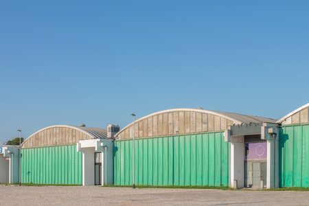 Row of green warehouses with rounded rooftops and blue sky Stock Photo - 106361711