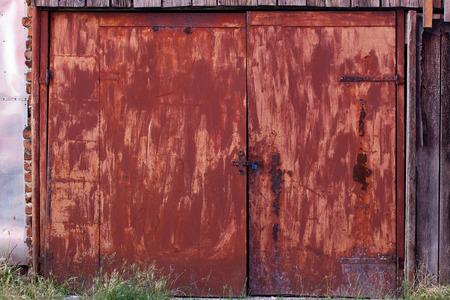 Old, rusty red double door, securely closed