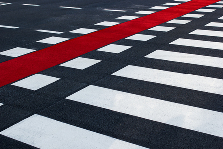 Diagonal shot of pedestrian crossing, with black and white stripes and red bike lane