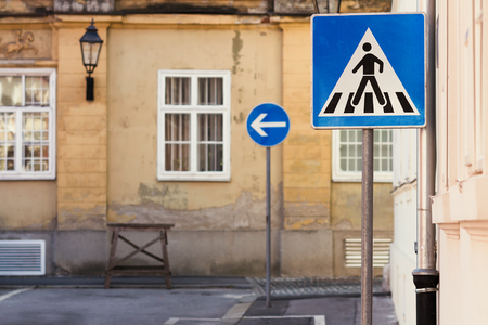 Blue traffic signs in front of an old building in Europe