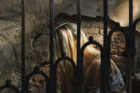 Sad and lonely blonde haired woman sitting behind the iron fence, hiding her face
