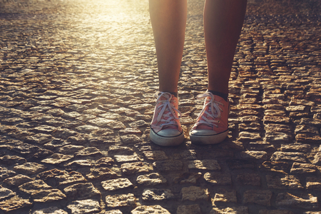 Woman in pink canvas sneakers standing on the cobblestone street in late afternoon sunlight Stock Photo